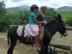 Jessica leads a donkey with a young girl riding. Beautiful countryside int eh background